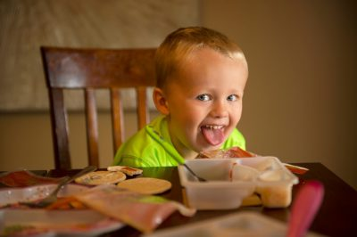 Photo: A little boy makes a face while eating his lunch.