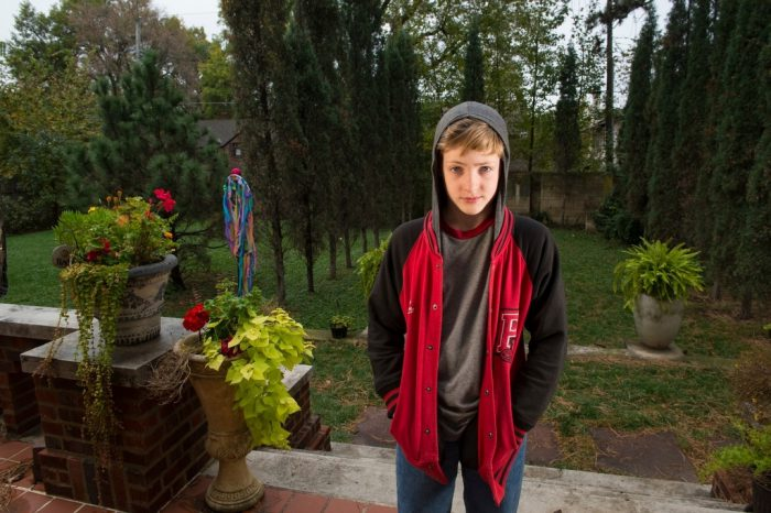 Photo: An adolescent boy wears a hooded sweatshirt.