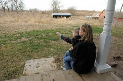 Photo: A mother and her son sit on the porch at a Nebraska farmhouse.