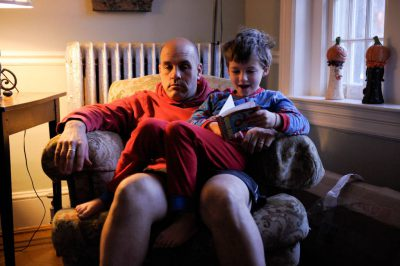 Photo: A son sits on his father's lap.