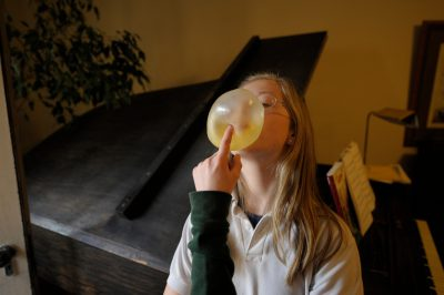 Photo: A girl blows bubble gum in her living room with some interference from her brother.