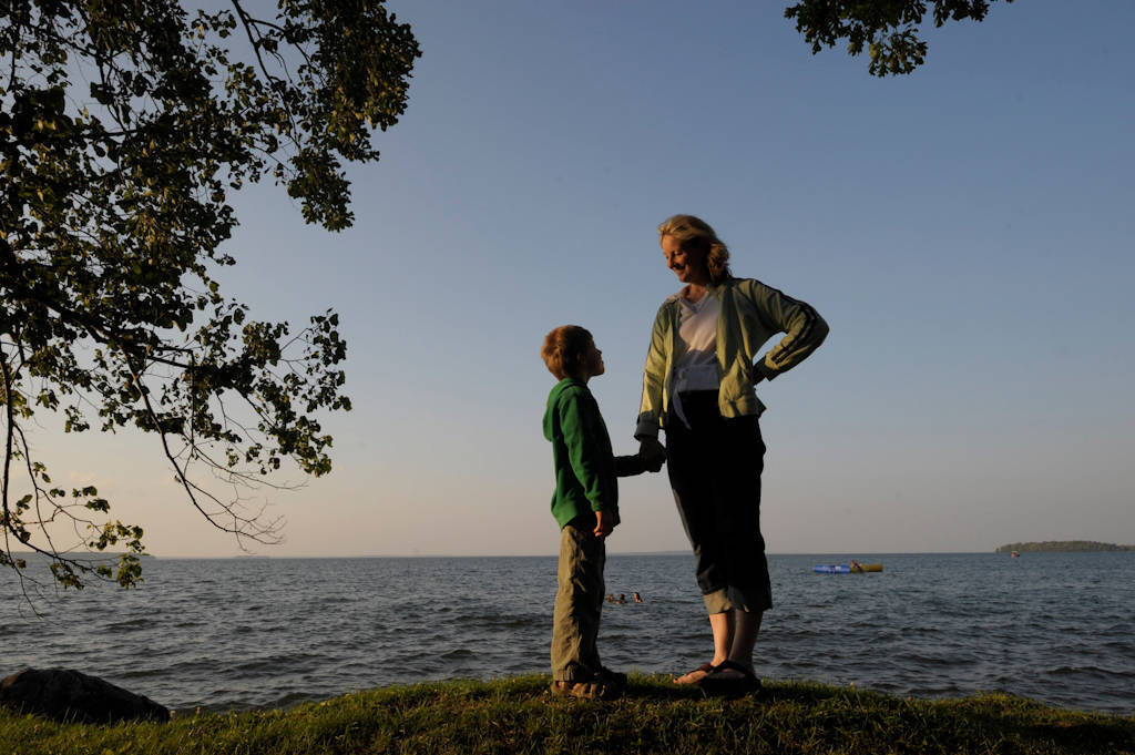 Photo: A mother and son hold hands together next to Leech Lake, Minnesota.