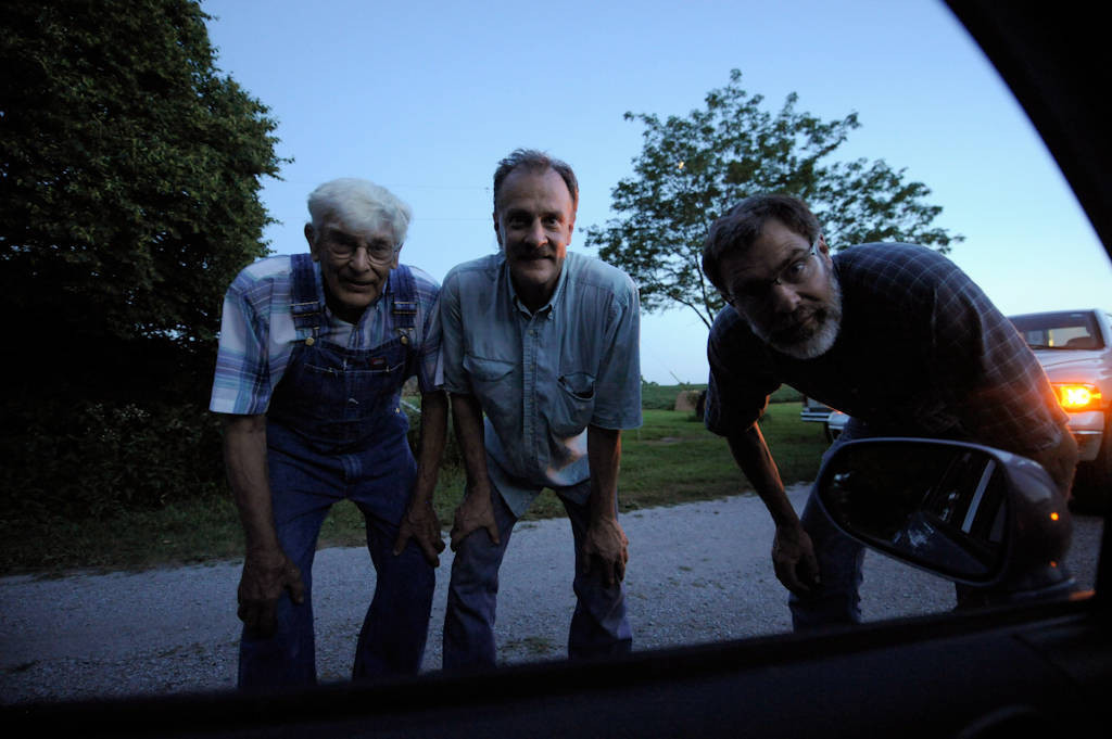 Photo: A father standing with his two sons looking into a car window at their farm in Cortland, Nebraska.