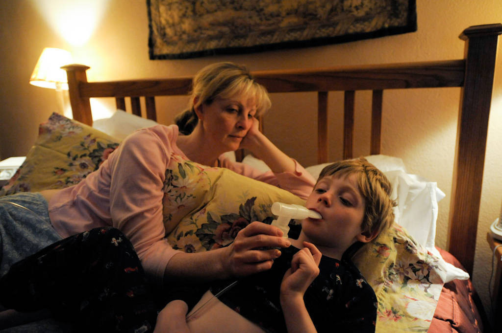 Photo: A woman uses a nebulizer on her son who was having trouble breathing at their home in Lincoln, Nebraska.