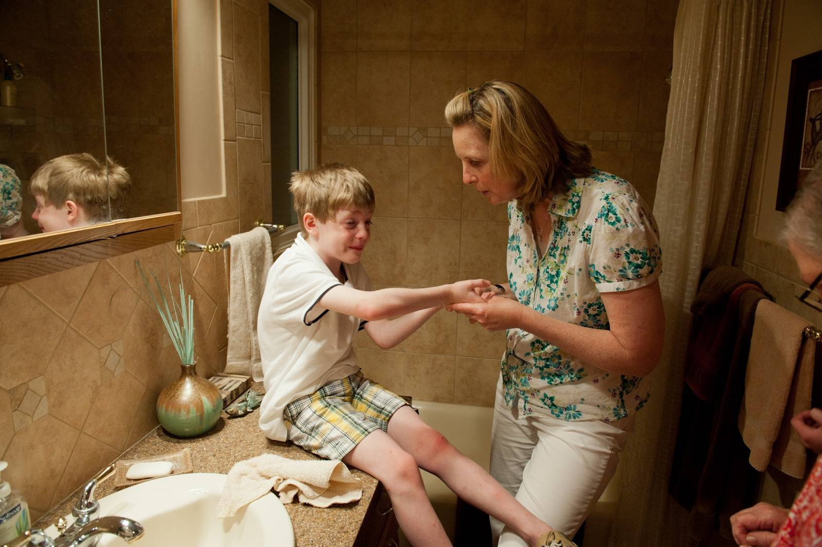 Photo: A mother tends to her son's scraped hand.