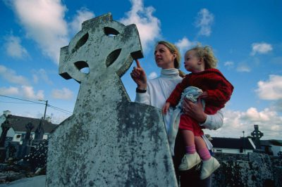 Photo: A mother and daughter read a headstone in a Celtic cemetery in Ireland.
