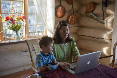 Photo: A mother shows her son how to use a computer.