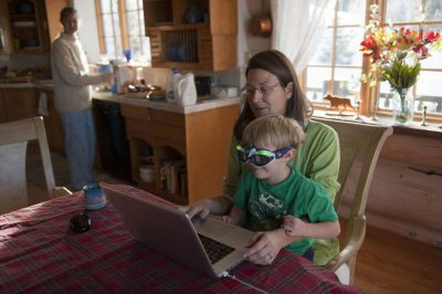 Photo: A mother helps her young son use a computer.