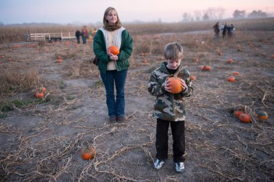 Photo: A young boy picks out a pumpkin.