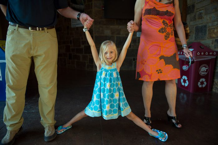 Photo: An elementary age girl smiles while holding her parents' hands.