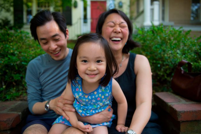 Photo: A family of three laugh together.