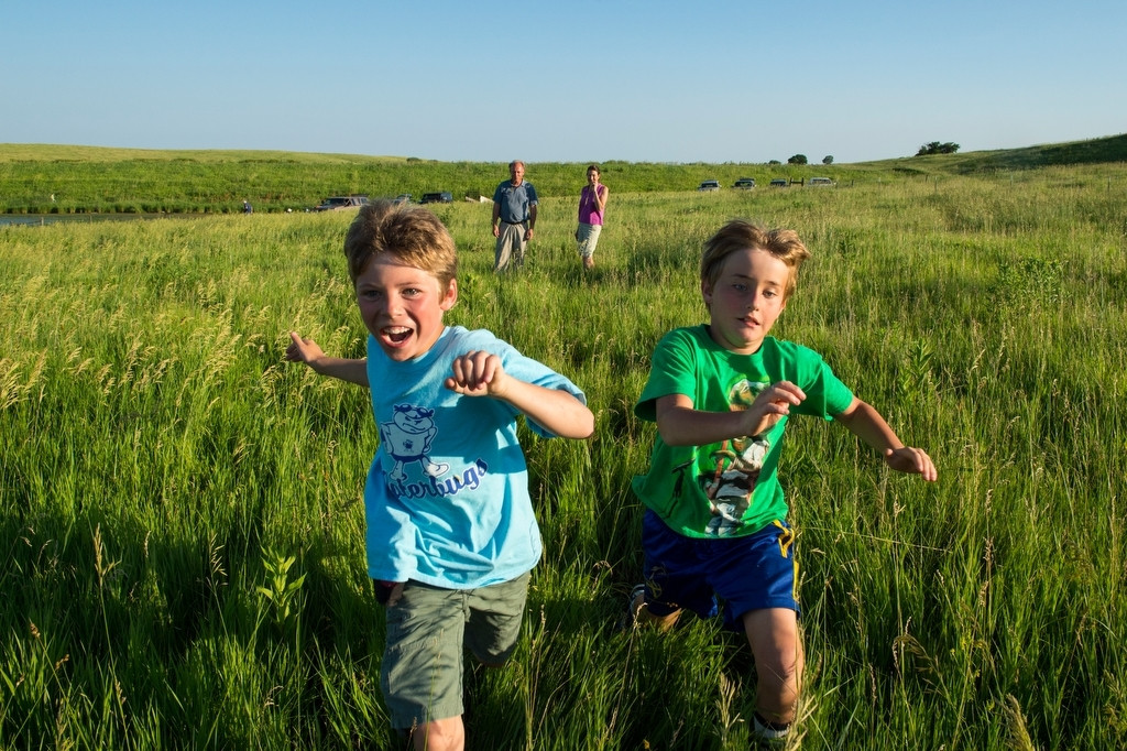 Photo: Two young boys run through grasses as their parents watch.