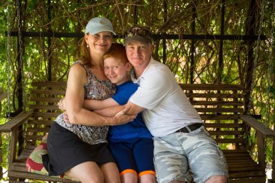 Photo: A family of three, hug and smile as they sit on a porch swing.