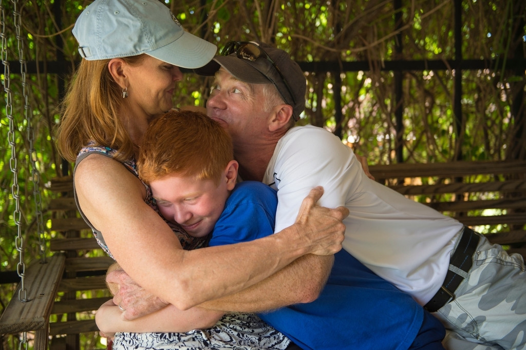 Photo: A family of three, hug as they sit on a porch swing.