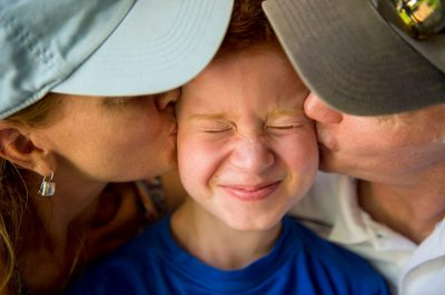 Photo: A mother and father kiss their elementary aged son on his cheeks.
