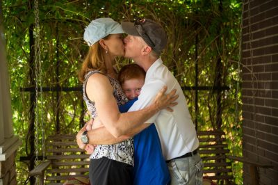 Photo: A family of three, hug and kiss as they sit on a porch swing.
