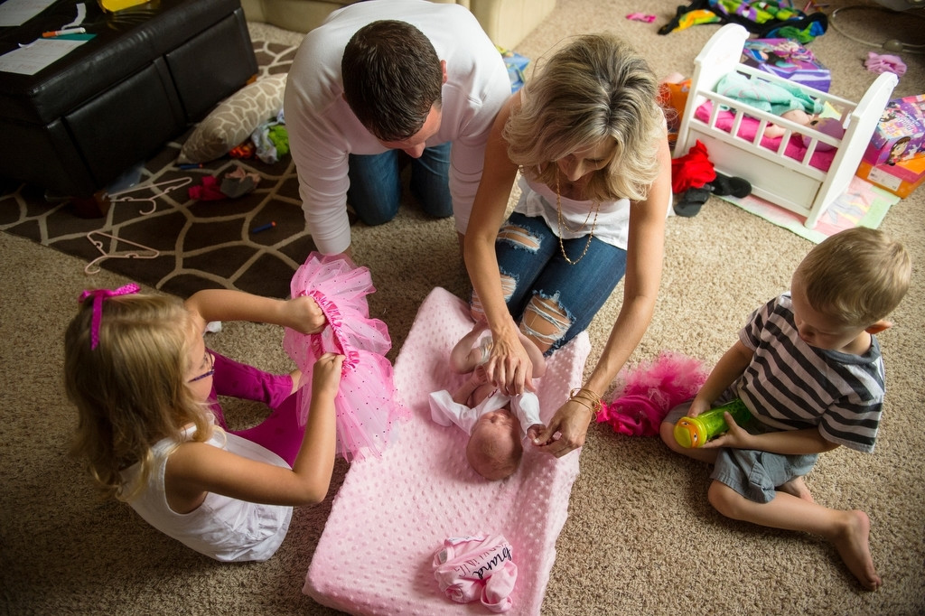 Photo: A family works together to change the clothes of their newest family member, a baby girl.