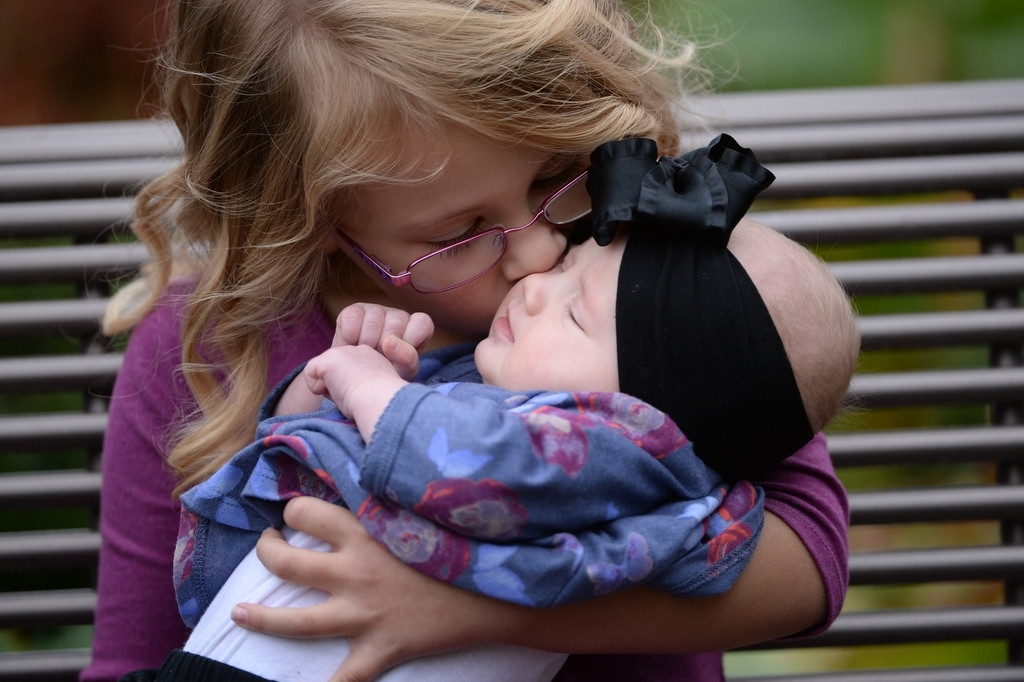 Photo: A little girl kisses her baby sister.