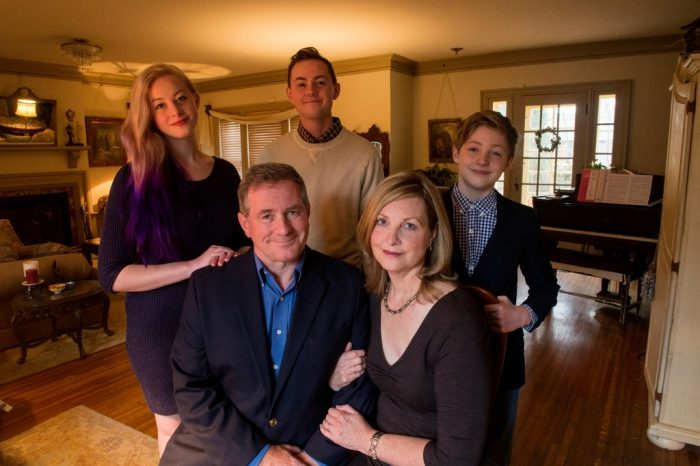 Photo: A family gathers for a portrait in their home.