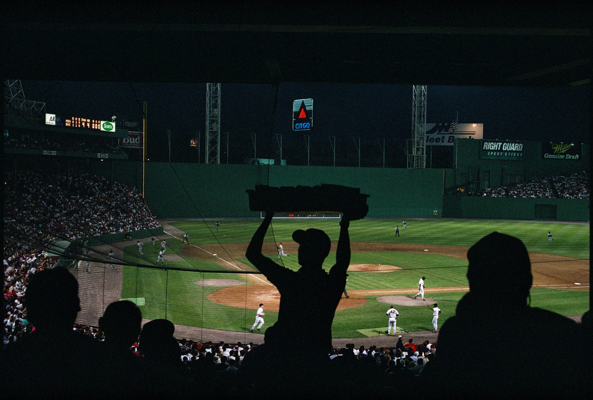 Photo: Fenway stadium during a night baseball game showing fans and players in Boston, Massachusetts.
