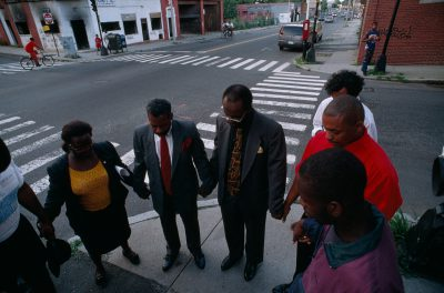 Photo: A reverend prays with residents of Roxbury before escorting a mayorial candidate through the area in Boston, Massachusets.