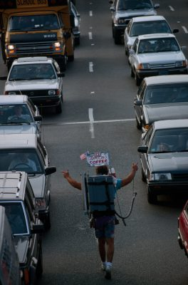Photo: Coffee vendor walking with commuter cars in line outside the Sumner tunnel in Boston, Massachusetts.