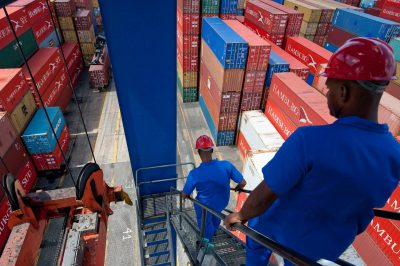 Photo: Workers in hard hats and uniforms walk among shipping containers at the port of Salvador, Brazil.
