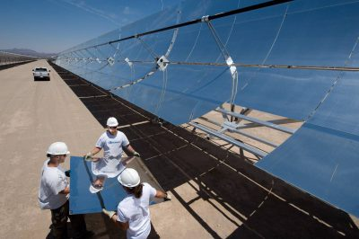 Photo: Workers handle a solar panel at a concentrated solar power plant in Nevada.