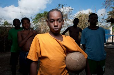 Photo: A young soccer player with his friends in Rio de Janeiro, Brazil.