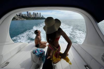 Photo: A young couple relaxes on a speed boat off the cost of Salvador, Brazil.