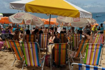 Photo: Colorful striped chairs crowd the beach in Salvador, Brazil.
