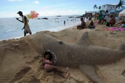 Photo: A young girl plays near a sand sculpture of a shark on the beach in Salvador, Brazil.