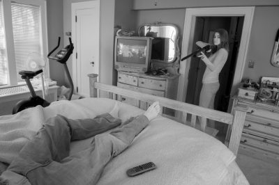 Photo: A young woman prepares to shoot a man in bed in Lincoln, Nebraska.