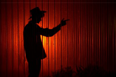 Photo: The silhouette of a young man wearing a cowboy hat and pointing his finger like a gun.