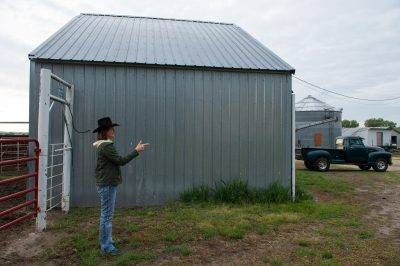 Photo: A woman wearing a cowboy hat points her finger like a gun as she stands next to a barn.