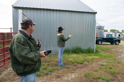 Photo: A man holds a flash unit and receiver as woman wearing a cowboy hat points her finger like a gun next to a barn.