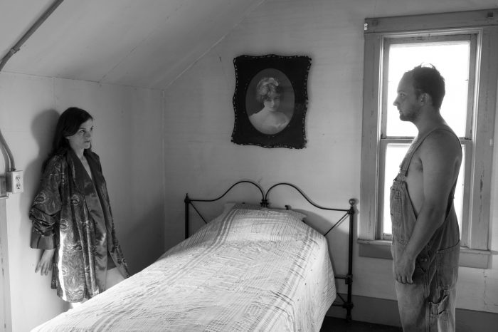Photo: A man and woman gaze at each other in a bedroom.