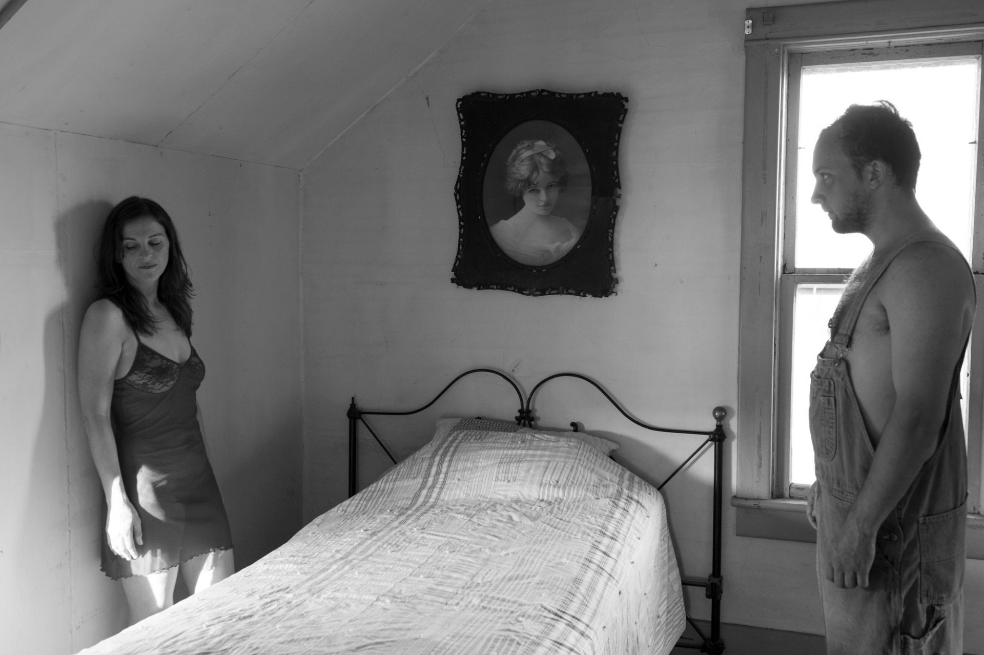 Photo: A man gazes at a woman in a bedroom while she looks away.