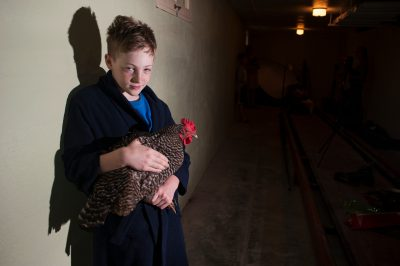 Photo: An elementary age boy holds a chicken in a basement.