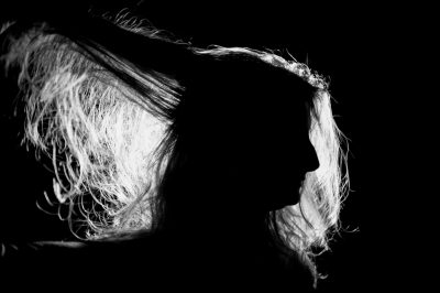 Photo: A woman's hair is illuminated by a light.