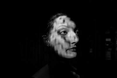 Photo: A woman's face is illuminated by a patterned light.
