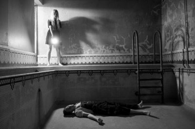 Photo: A young man appears to lie dead in an empty swimming pool as a young woman looks on.
