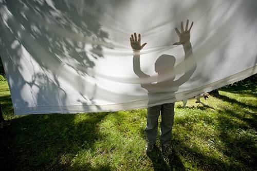 Photo: A boy stands behind a bed sheet in a back yard.