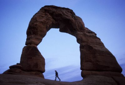 Photo: Hiker at Delicate Arch at Arches National Park, Utah.