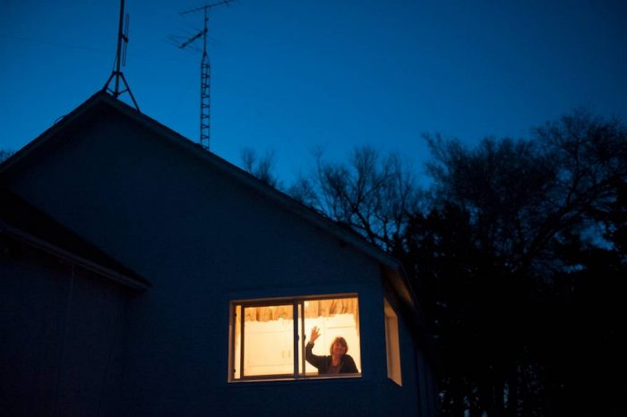Photo: A woman waves from her ranch house at night.