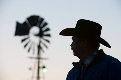 Photo: A silhouette of a rancher looking off in the distance.