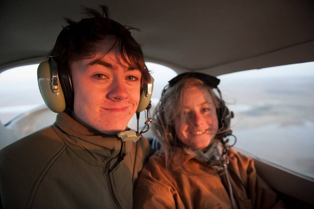 Photo: Two teenagers in the cockpit of an airplane.
