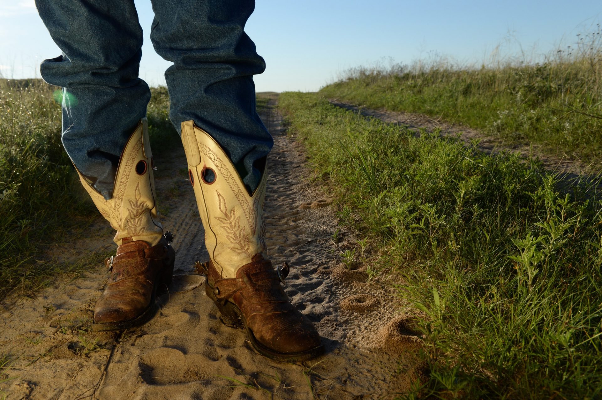 Photo: A cowboy stands on a country road in the Nebraska Sandhills.