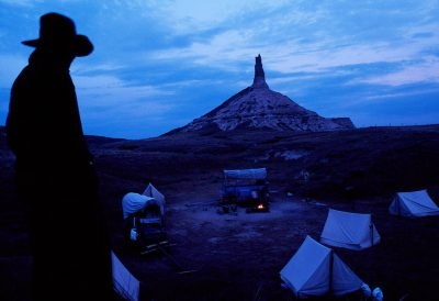 Photo: A member of a group re-enacting the westward migration relaxes at a camp near Chimney Rock in Nebraska.
