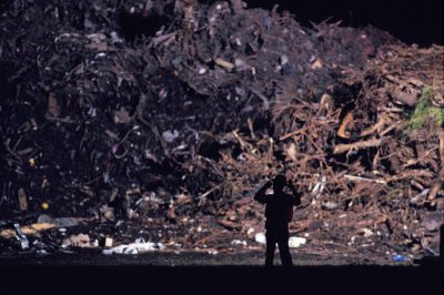 Photo: A man stands in front of a mountain of debris left by Hurricane Andrew.